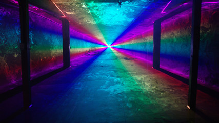 Rainbow laser light tunnel shines past columns at nightclub, background 2