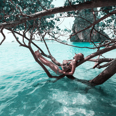 Tourist female resting in the branches of mangrove at Phra Nang Beach, Krabi, Thailand
