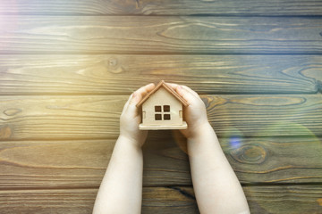 house in the hands of a child on a wooden background. family, affordable housing, mortgage.