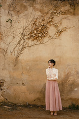 Young woman posing against wall with dry foliage