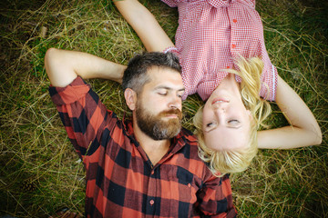 Hipster and girl enjoy summer day on nature. Couple in love relax on green grass. Bearded man and woman with long blond hair. Summer vacation concept. Love romance and family