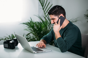 young man using his mobile and working in his office. business concept