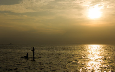 Silhouette of a couple on paddle board on the open sea at sunset in the island of Koh Pha Ngan, Thailand