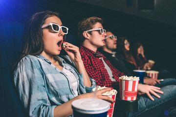 Amazed and surprised people are sitting in one row and watching movie. Blonde girl is eating popcorn with amazement on her face because of movie. The other people are amazed as well.