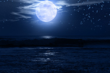 Exotic Moon and stars rising from the ocean horizon.
