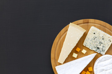 Various types of cheese on round wooden board, top view. Dark background. Copy space. Flat lay. From above.