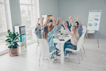 Confident, stylish, executive, attractive lucky colleagues using gadgets sitting in modern office with hands up celebrating successfully completed project, screaming, yelling, full of happiness