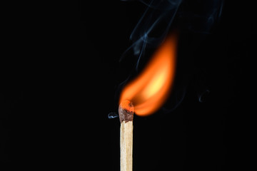 Match with a flame flaring point beveled on its side on a black background closeup