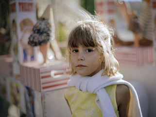 Portrait of a young girl standing next to an ice cream truck.