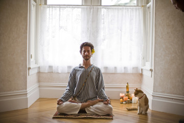 Portrait of a mid-adult man meditating with cat on a mat with his legs crossed inside his home.