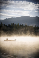 man in canoe in foggy lake