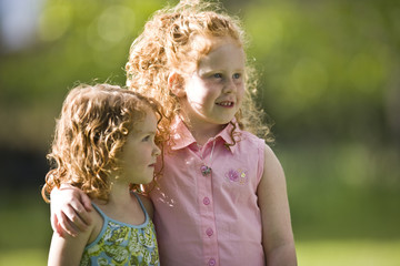 Young girl standing with her arm around her younger sister outside in the sunshine.