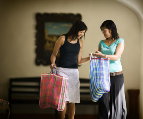 Two women smile as they carry their shopping bags.