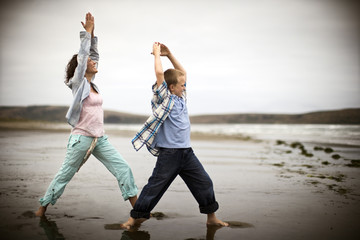 A mother and a son are exercising on a beach.