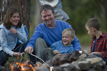 Happy family sitting around a campfire and toasting marshmallows in the forest.