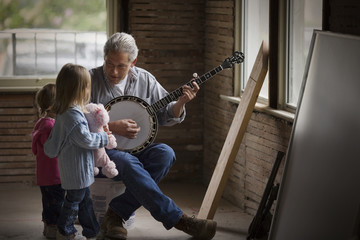 Mature man playing a banjo to his two young daughters.