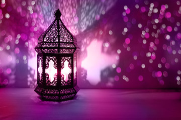 Ornamental Arabic lantern with burning candle glowing at night and glittering colorful bokeh lights. Festive greeting card, invitation for Muslim holy month Ramadan Kareem. Blurred party background