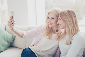 Stylish trendy modern cheerful mother and daughter having smart cell phone in hand shooting self portrait on front camera sitting on sofa in living room enjoying free time
