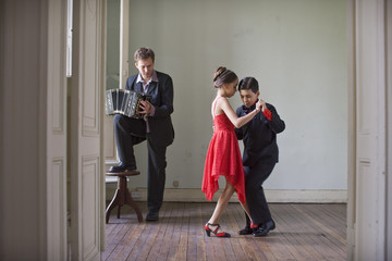 Boy and girl dancing in a room while a young man plays an accordion.