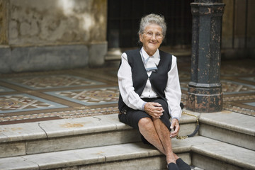 Portrait of a senior adult woman sitting on a step in a foyer.