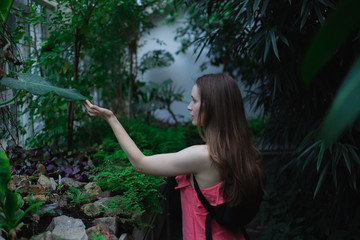 Young brunette woman, wearing pink dress, in botanical garden touching a big leaf