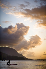 Scenic view of a surfer waiting on a calm sea with coastline and clouds lit by a sunrise.