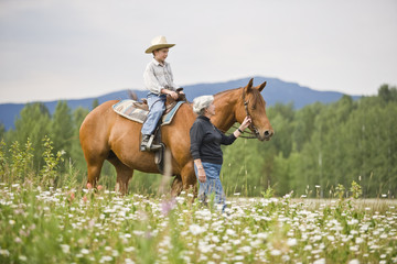 Grandmother leading horse ridden by grandson