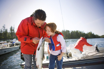 Teenage girl and her younger sister looking inside the mouth of a caught fish.