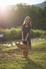 Portrait of a young girl holding a basket of flowers on a farm.
