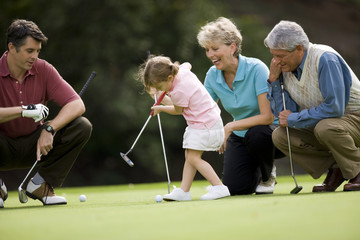 Family teaching young daughter to play golf