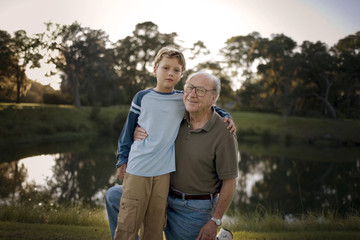 Portrait of a boy with his arm around his senior grandfather's shoulders.