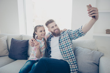 Cute girl with bearded stylish father in casual outfit checkered shirts sitting on couch in house embracing shooting self portrait on front camera showing peace symbol holding cell smart phone in hand