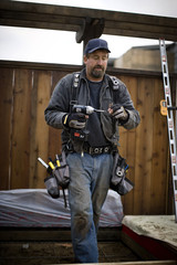 Male construction worker carrying an electric drill.