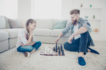 Portrait of family with one parent, stylish trendy kid and daddy playing chess moving figures sitting on carpet near sofa in modern livingroom indoor, style, lifestyle, hairstyle, casual outfit