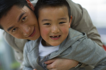 Portrait of a mid-adult man hugging his young son.