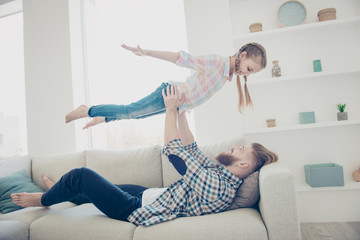 Side view portrait of family with one parent, strong stylish father lying on couch lifting up his daughter making plane holding hands to the side enjoying time together indoor in modern house