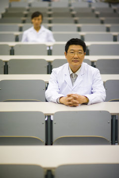 Portrait of male teacher in lab coat sitting in lecture hall