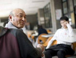 Senior adult man sitting and eating in a cafeteria.