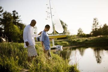 Father and son standing next to pond with model boat