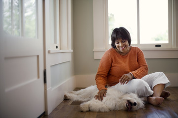 Middle-aged woman smiles and relaxes by petting her dog on the floor.