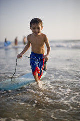 Boy running in the ocean with his boogie board