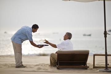 Beach resort waiter serving wine to man on sun lounger