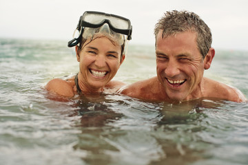 Portrait of a happy mid adult couple swimming in the ocean together.