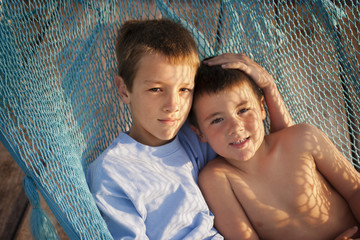 Portrait of two brothers lying in a hammock together.