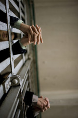 Hands of a young adult businessman and a colleague through bars of a prison cell in a derelict building.