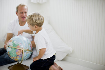 Father looking at a globe of the world with his son.