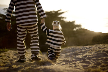Young boy walking hand in hand with his father while wearing a striped prisoner uniform on a beach at sunset.
