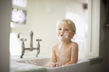 Portrait of a toddler having fun while taking a bubble bath.