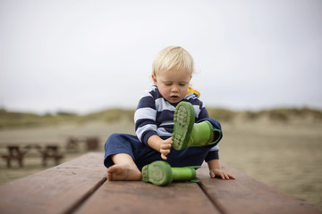 Boy removing his boots while sitting on bench outdoors