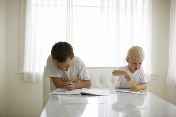 Young boy sitting at a dining table doing his homework with his younger brother.